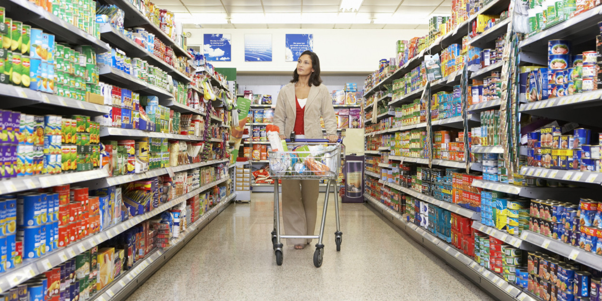 Woman shopping in supermarket, pushing trolley in aisle